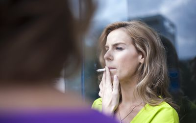 Young woman smoking cigarette outside office building