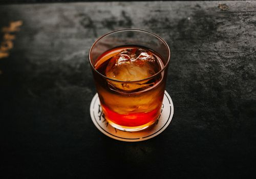 Cocktail on a paper coaster on a black tabletop