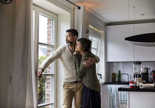 Pensive man staring out window with arm around woman