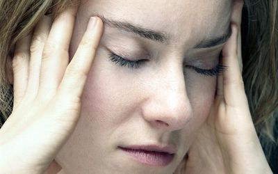 young woman with headache and holding her temples