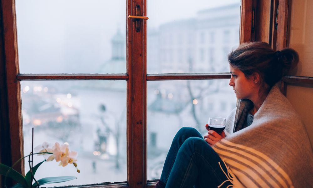 Depressed woman sitting near the window
