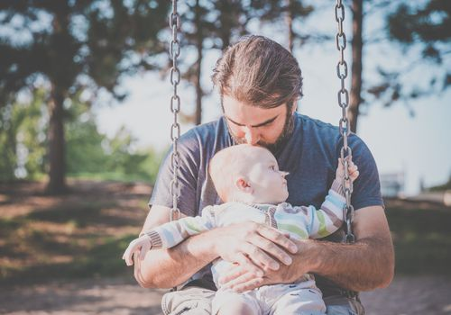 man holding a baby on a swing