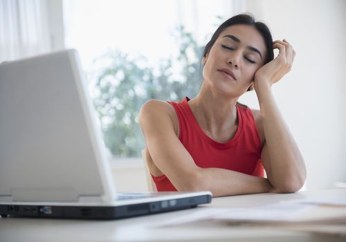 woman with eyes closed in front of laptop