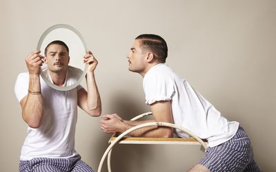 man lean across a table looking at himself in a mirror held by another man who looks just like him