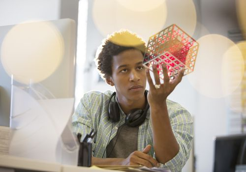 Young man at computer holding cube