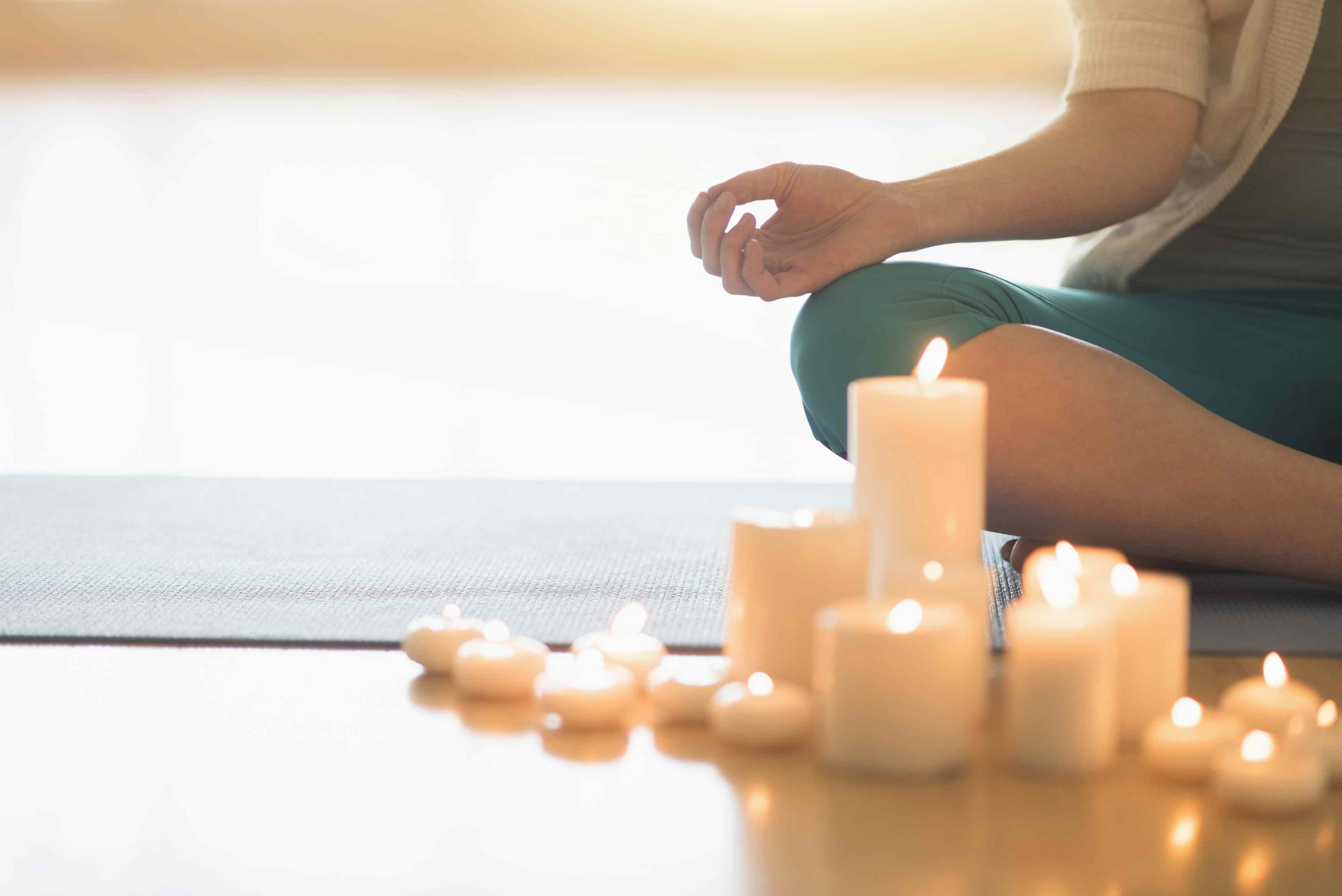 Woman meditating with candles in the foreground