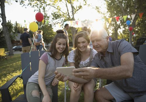 Grandfather and granddaughters taking selfie with camera phone at summer neighborhood block party in park