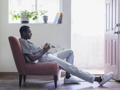 A man relaxing in a chair while looking at his phone.