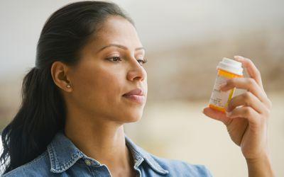 Hispanic woman reading medication