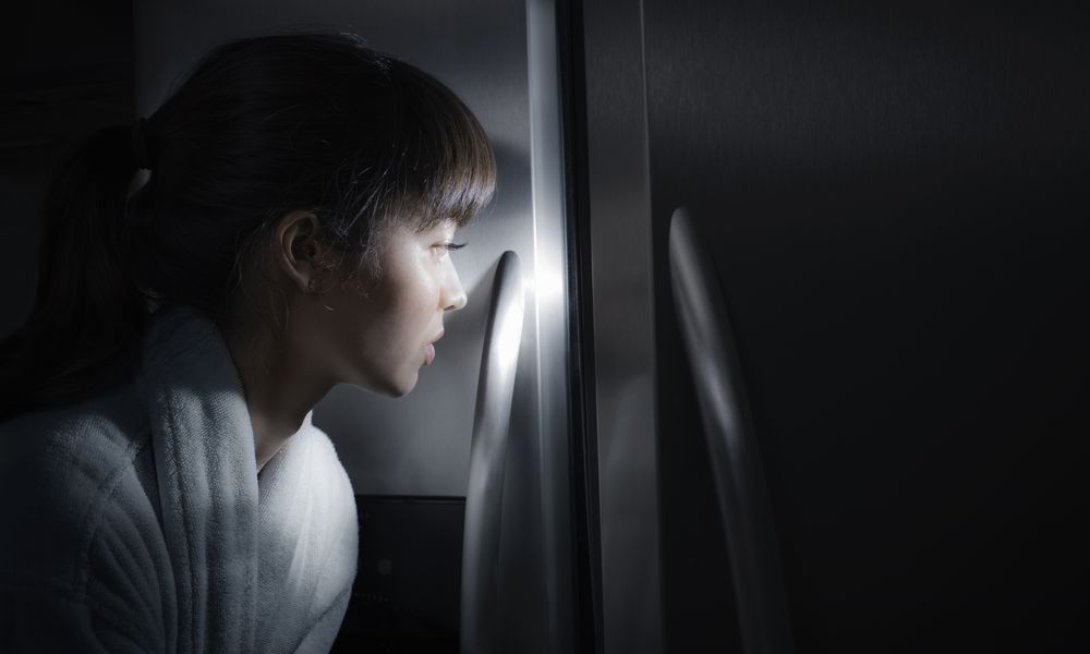 Mixed race woman peering into refrigerator at night