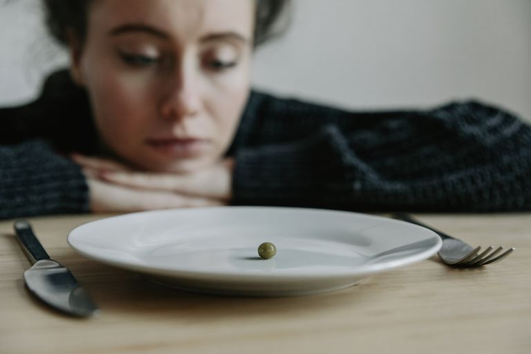 Woman staring at a plate with one pea on it