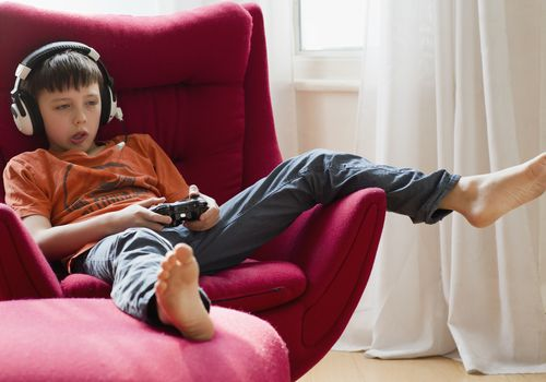 Boy sitting in chair, playing video games