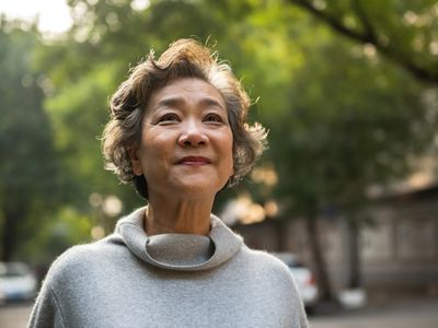 Portrait of cheerful senior woman relaxing outdoor, standing on the road in the city