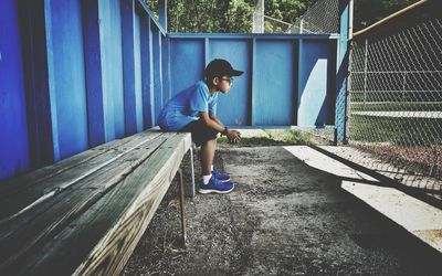 Full Length Of Boy Sitting On Bench