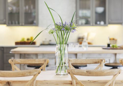 Fresh flowers in a vase on a wooden table