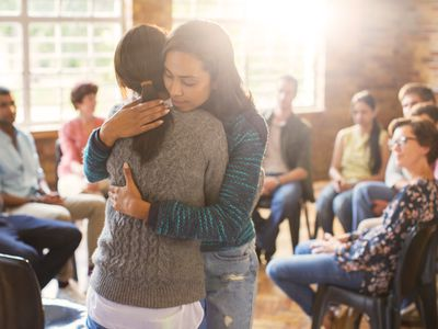 woman receives support at a group meeting