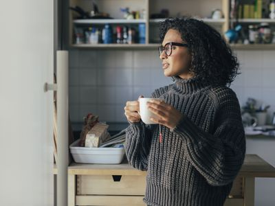 Woman Drinking Hot Tea in the Kitchen