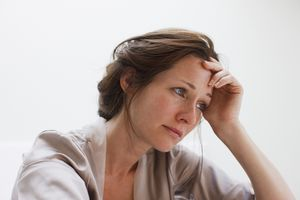 Depressed woman with head in hands.