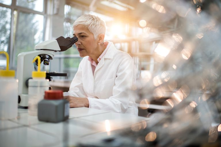 Woman in labcoat looking through a microscope