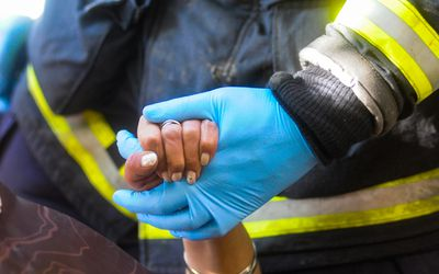 firefighter holding a Black woman's hand