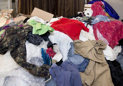 Large messy pile of household items, clothes, boxes, hangers, bubble wrap, toilet paper, pants, shirts, dresses with curtains and mirror in background