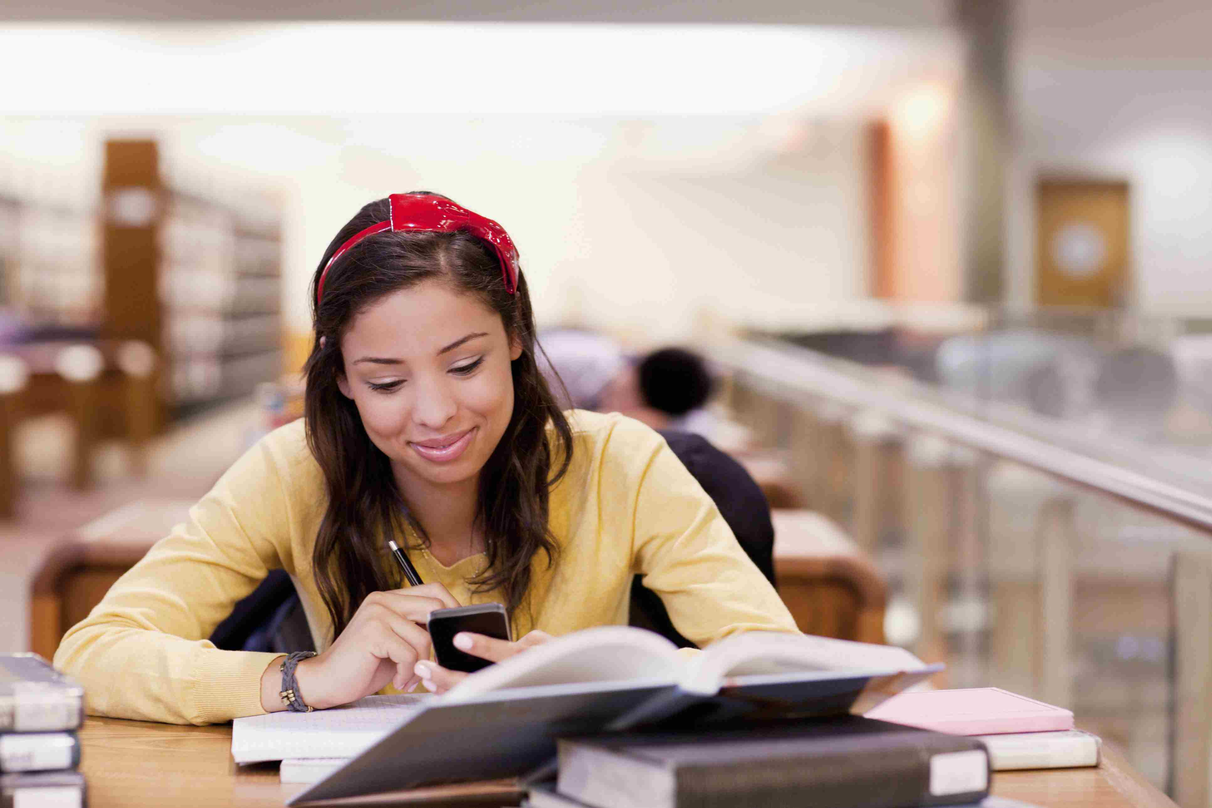 Young woman studying and using her smartphone in a library
