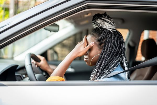 Woman driving in car with head in hands.