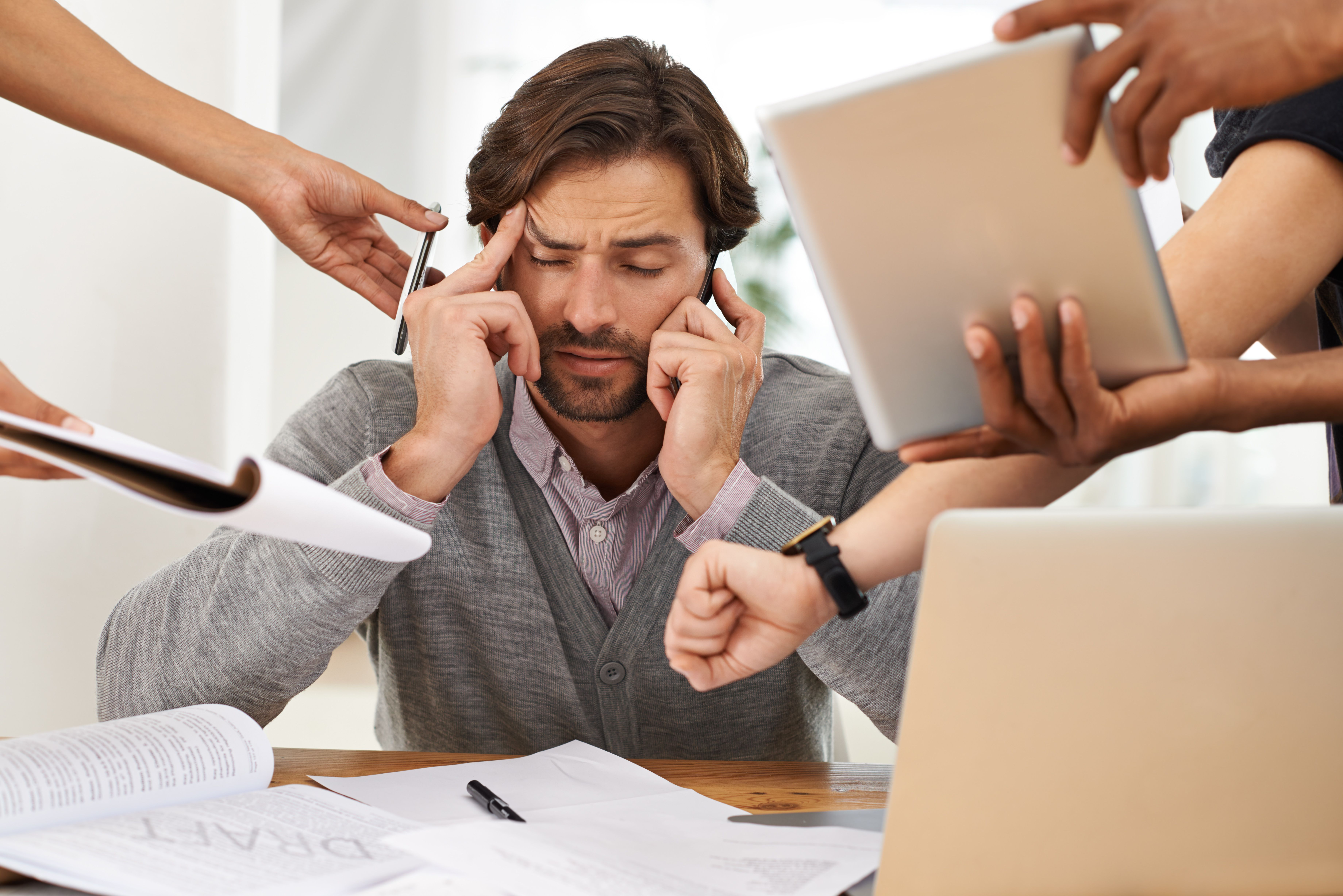 Man in an office with many things being shoved in his face