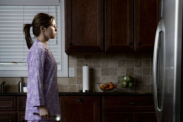 Woman in pyjamas, looking at refrigerator