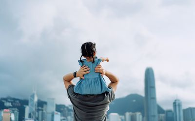 Rear view of young Asian father giving little daughter piggyback ride by the promenade
