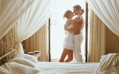 Young couple kissing in doorway of balcony, bed in foreground