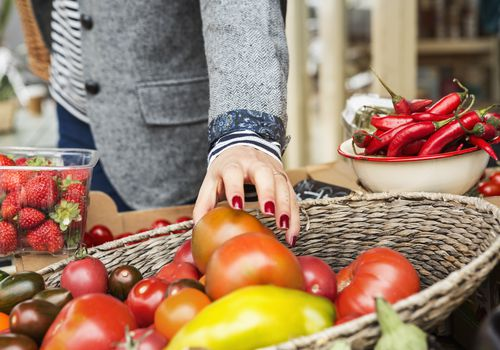 Woman's hand reaching for a tomato at a market