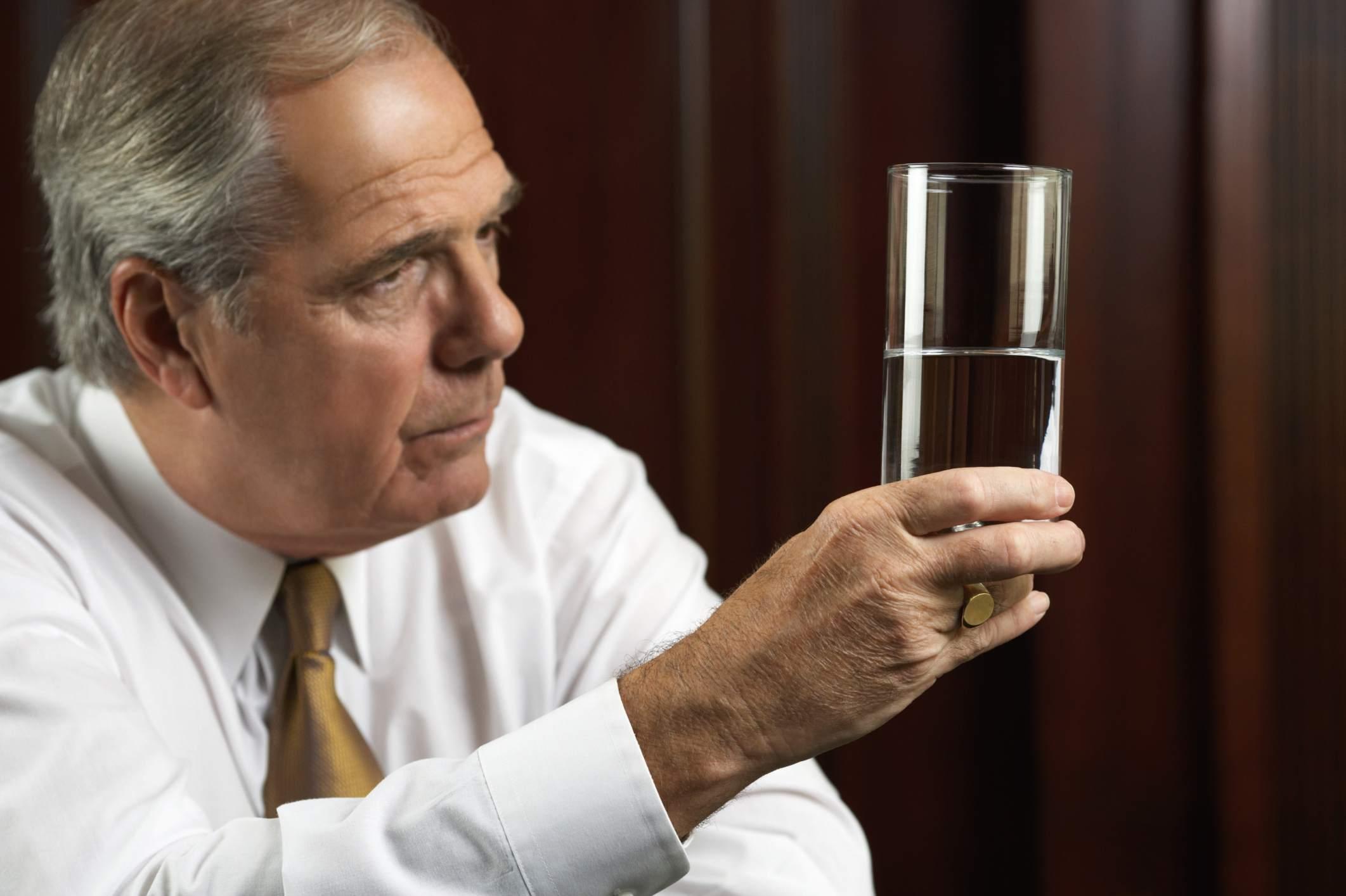 senior man looking at half full glass