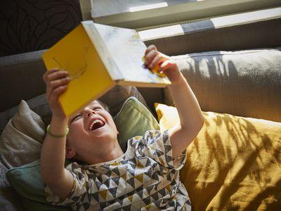 Boy lying down reading book laughing