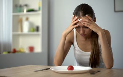Woman looking at small portion of food on her plate.