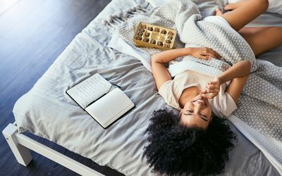 BIPOC woman on bed with chocolates and a journal