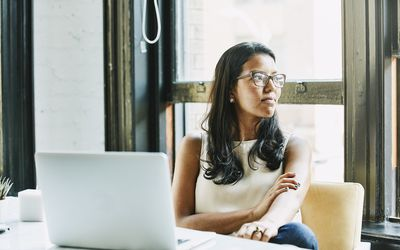 Woman with glasses staring happily out window. Deep in thought.