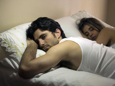 Couple in bed at night, woman sleeping, man awake