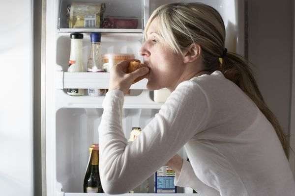 Woman eating from the fridge at night