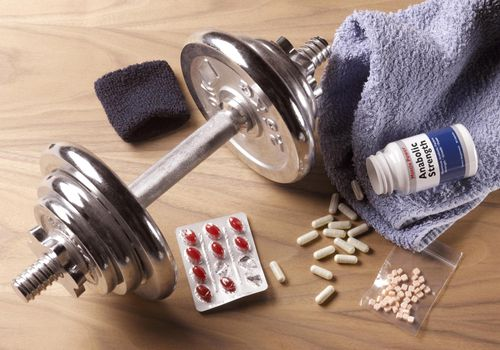 Dumbbell and anabolic steroids on a wooden floor