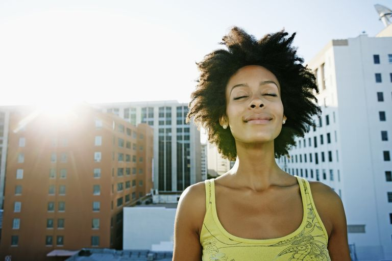 Woman smiling with eyes closed on urban rooftop
