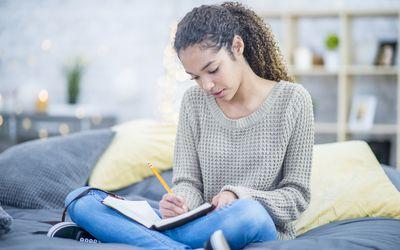 Teenage girl journaling on her bed