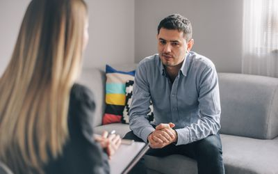 A photography of a man talking to his therapist.