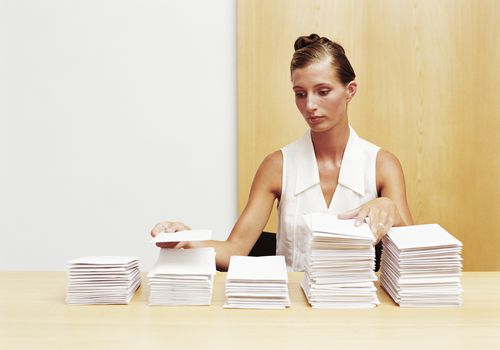 Woman carefully stacking neat piles of papers.