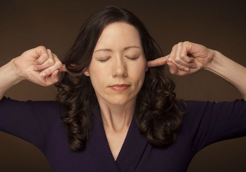 Woman with fingers in her ears and closed eyes