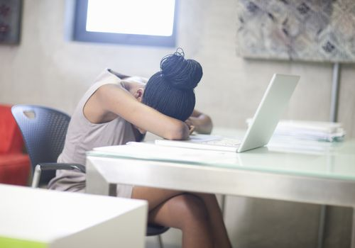 Woman with her head on a table in front of a laptop