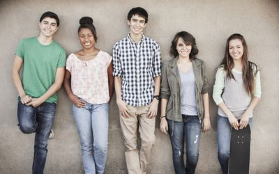 teenagers leaning against wall