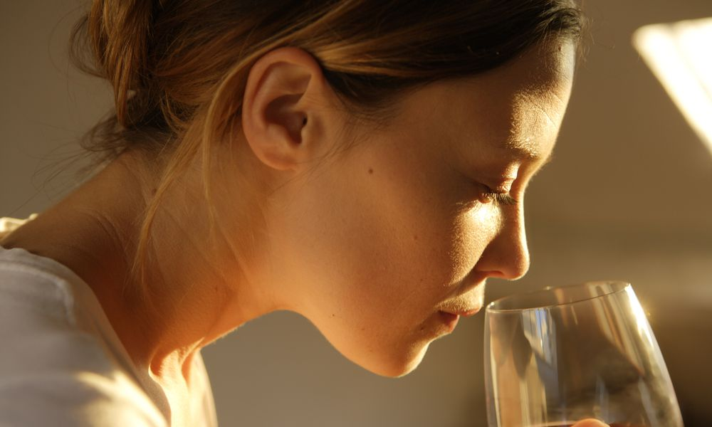 Woman contemplating whether to drink alcohol because she is taking Lexapro.