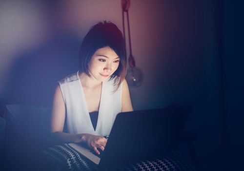 woman using laptop in a darkened room