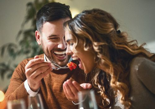 Closeup of mid 20's couple having fun during dinner party. The guy is feeding his girls with some chopped fruit, both laughing.